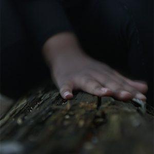 Hand on dark wood