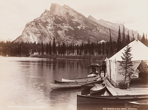 Man with boats in Bow River in front of Twin Peaks in Banff
