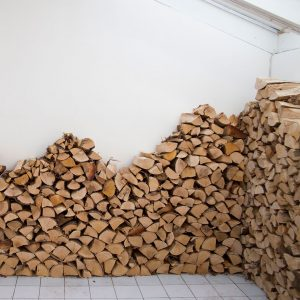 piles of wood in a corner of a white room.
