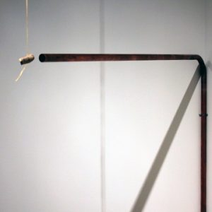Unidentified animal bone dangling in front of bent copper pipe