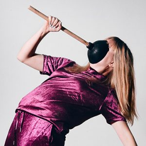 Woman holding a plunger on to her face