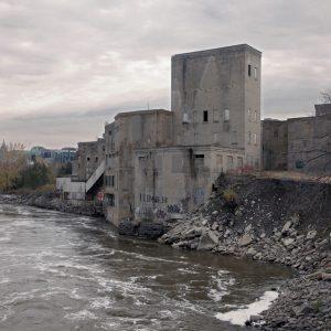 Run down building next to a river bank