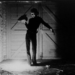black and white still of a person holding a rock in a dark brick room