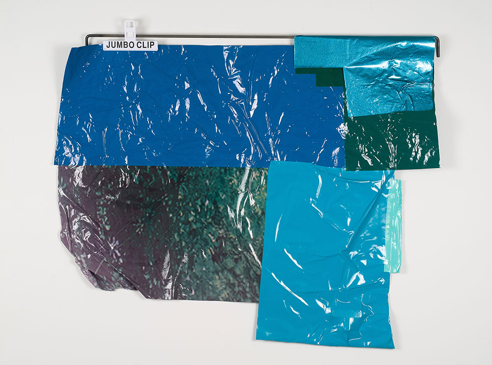 pieces of blue plastic against a white wall being held up by a white