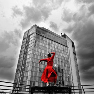 person dressed in red in a dance pose in-front of a large apartment building. the background is entirely grey