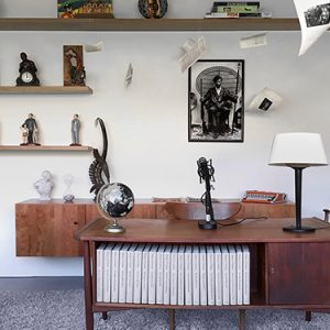room with a brown wooden desk, figurines on shelves, a lamp, books, microphone and globe on desk.