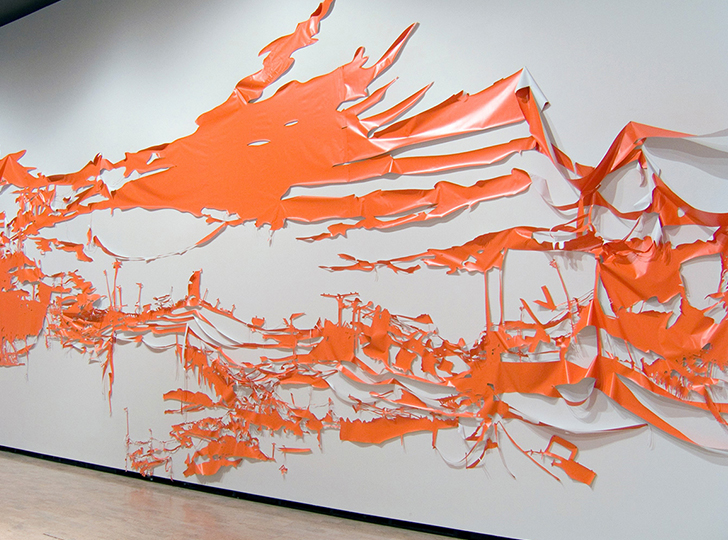 orange shredded material cascading off of a white wall