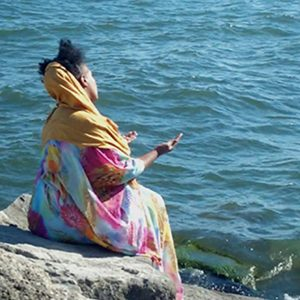 woman sitting by a lake starring at the water in a meditative pose