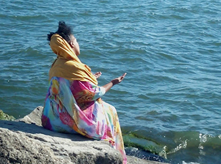 a woman by a lake starring at the water in a meditative pose