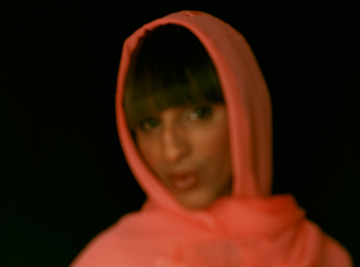 figure of a person with long brown bangs wearing an orange-pink headscarf