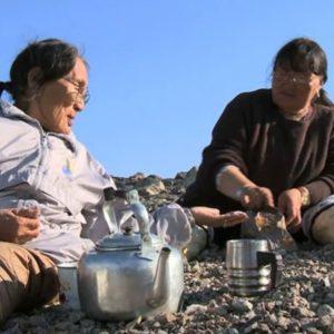 two inuit people drinking tea