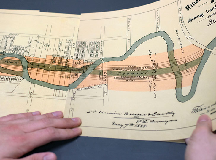 Artist holding image of River Don Straightening Plan.