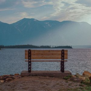 Empty bench looking out at still Atlin Lake and mountains in the distance