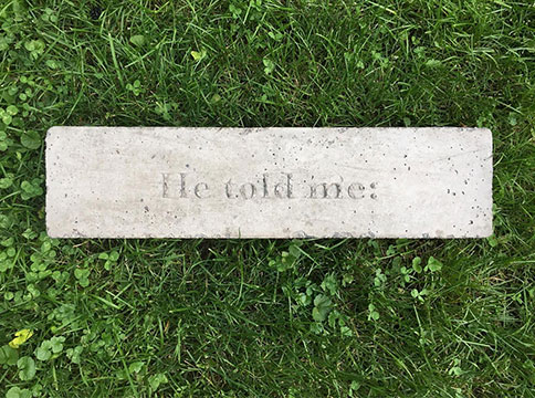 "A photograph showing a slab of concrete engraved with the words ""He told me:"" photographed against a background of green grass. Work by Jasmine Canaviri."