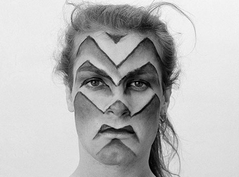Lorenza Böttner, with zigzag lines painted horizontally across her face, staring straight into the camera.
