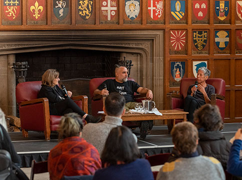 Rebecca, Osvaldo, and Barbara in conversation in front of audience in great hall