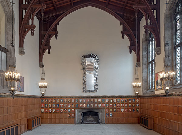 Mirrored long dining table with silver reflective tablecloth installed in Hart House's Great Hall.