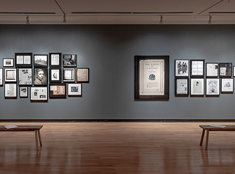 Gallery with two benches, and a grey wall with a collage of picture frames