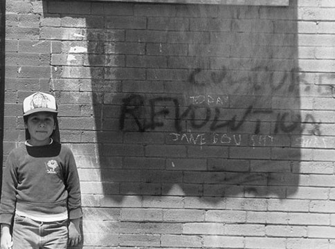 A young girl standing in front of a brick wall with 'Culture Revolution' spray-painted on the surface.