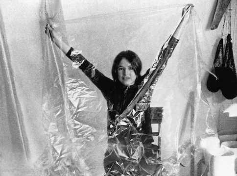 Black and white photo of Eva Hesse in her studio holding up a plastic sheet