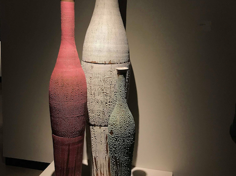 red, beige , and green tall vases on display