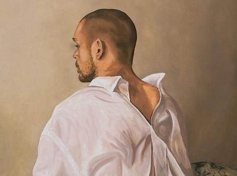 Man in white shirt facing a beige wall