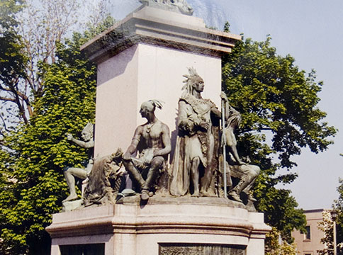 Bottom of statue with Indigenous men crouched and seated