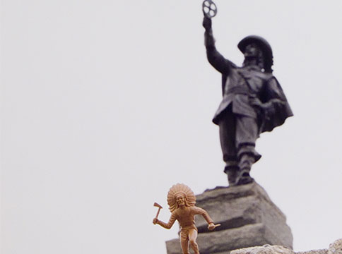 Small statue of Indigenous man in headress in front of larger statue of Samuel de Champlain