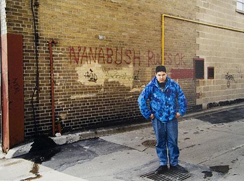 "Man in blue jacket posing in front of graffiti reading ""nanabush rules ok"""