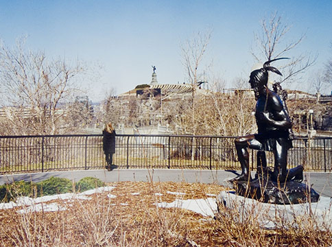 Metal statue of kneeling man, and woman in the distance looking at far away statue