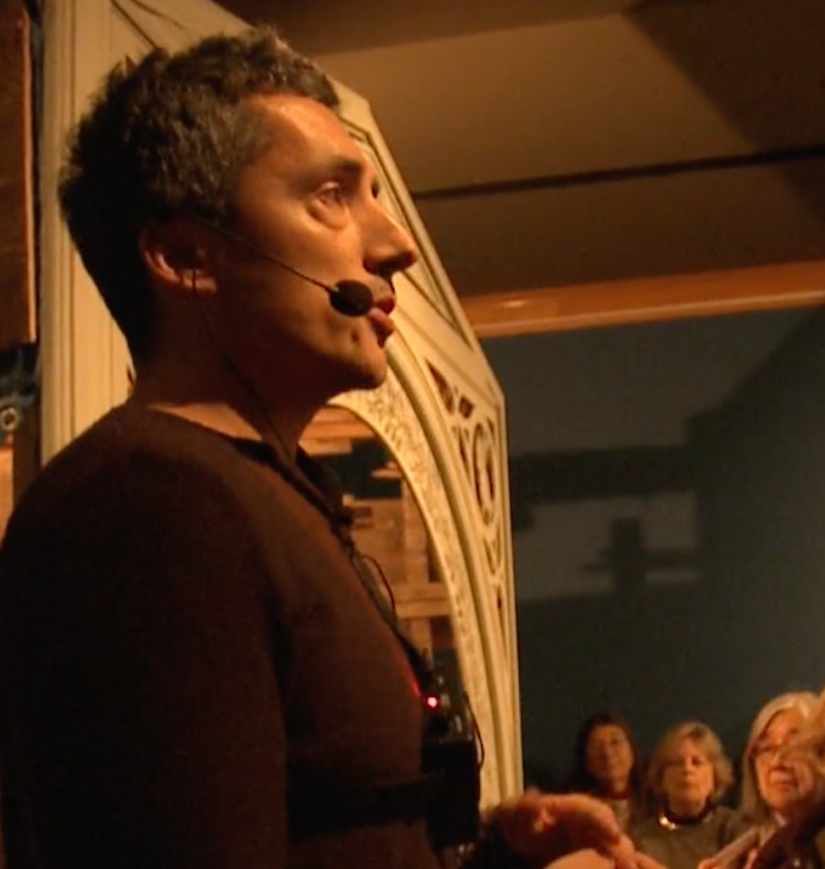 Kent Monkman with microphone talking to audience