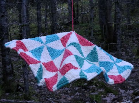 White, blue, teal, and pink tapestry hanging in the forest