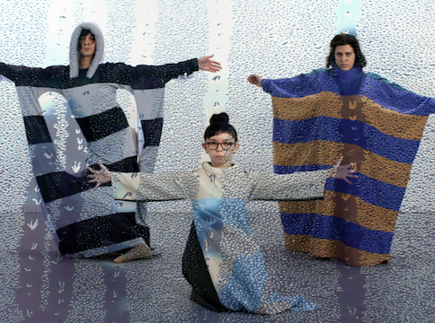 Rainy window looking into Girl kneeling in white in front of two women standing with striped outfits
