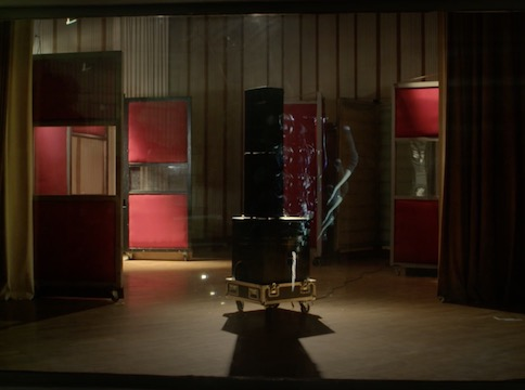 Dark room with red panels and speakers on wheels in the centre
